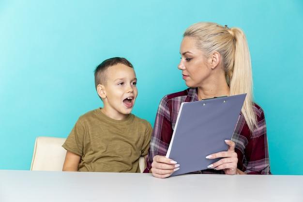 Jeune petit écolier à faire ses devoirs avec sa mère, coopération en famille, parentalité.