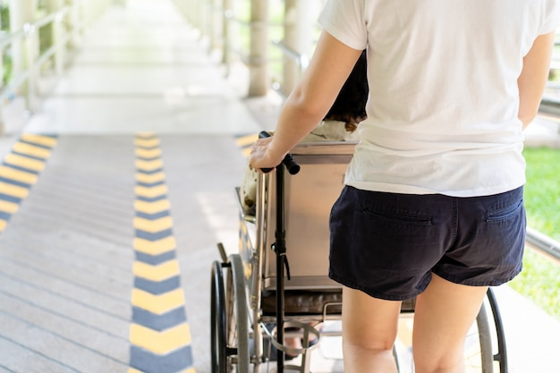 Jeune petit-enfant asiatique en prenant soin de sa grand-mère assise sur un fauteuil roulant.