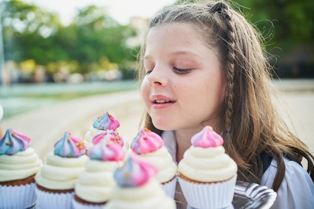 Jeune petite étudiante sentant les cupcakes dans le parc