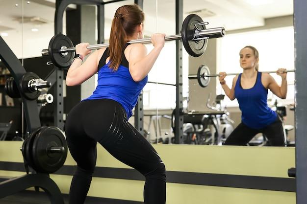 Jeune petite femme effectue l'exercice squat avec haltères dans la salle de gym