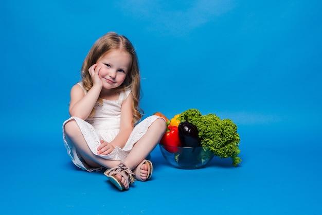 Jeune petite fille avec des légumes sur un mur bleu