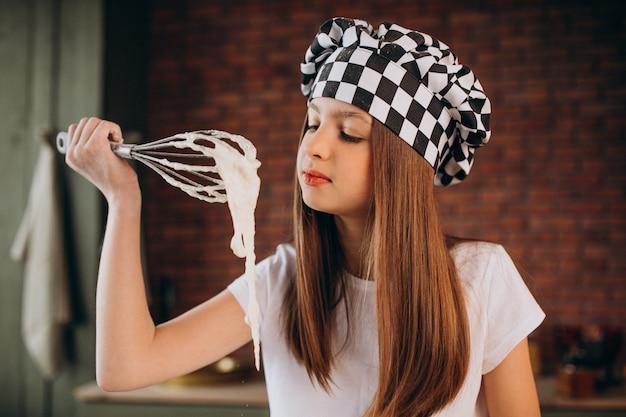 Jeune petite fille, pâtisserie à la cuisine pour le petit déjeuner