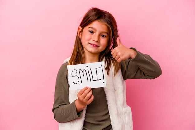 Jeune petite fille tenant une bannière de sourire sur fond rose