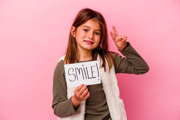 Jeune petite fille tenant une bannière de sourire sur un mur rose