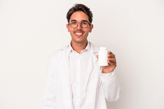 Jeune pharmacien homme de race mixte tenant des pilules isolées sur fond blanc heureux, souriant et joyeux.
