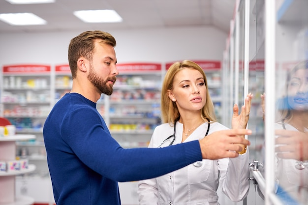 Jeune pharmacienne aidant un client masculin malade