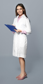 Jeune pharmacienne avec presse-papiers sur fond gris