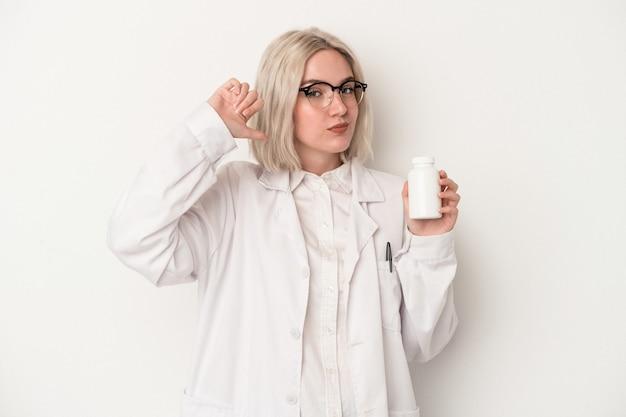 Une jeune pharmacienne tenant des pilules isolées sur fond blanc se sent fière et confiante, exemple à suivre.