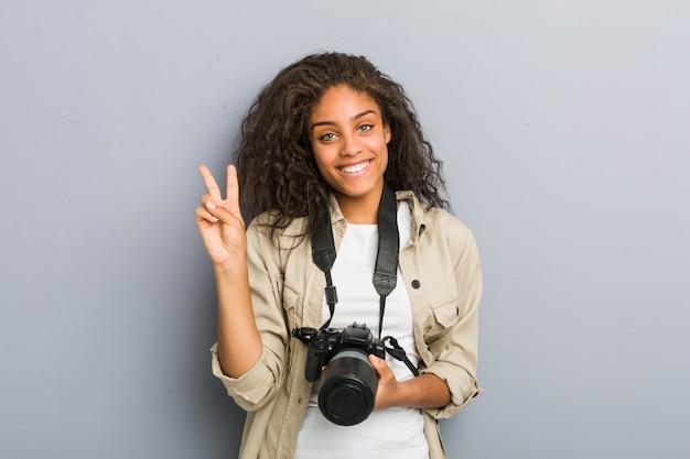 Jeune photographe afro-américaine femme tenant un appareil photo montrant le numéro deux avec les doigts.