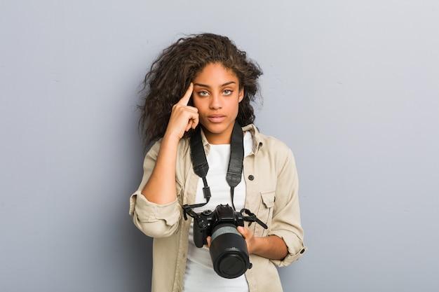 Jeune photographe afro-américaine femme tenant un appareil photo pointant son temple avec le doigt, pensant, concentré sur une tâche.