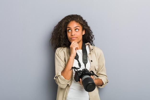 Jeune photographe afro-américaine femme tenant un appareil photo à la recherche sur le côté avec une expression douteuse et sceptique.