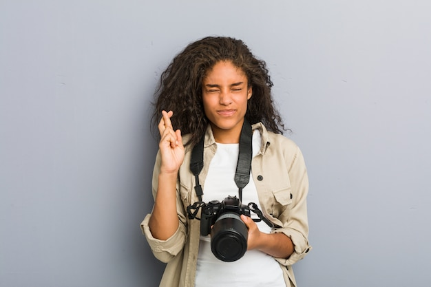 Jeune photographe afro-américaine femme tenant une caméra croise les doigts pour avoir de la chance