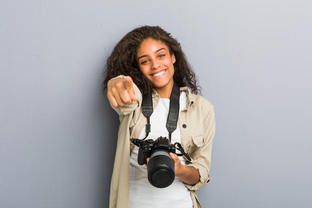 Jeune photographe afro-américaine femme tenant une caméra sourires joyeux pointant vers l'avant.
