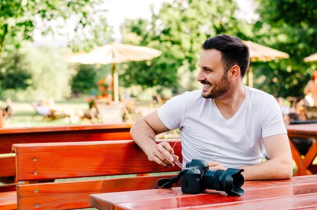 Jeune photographe assis dans un café à l'extérieur