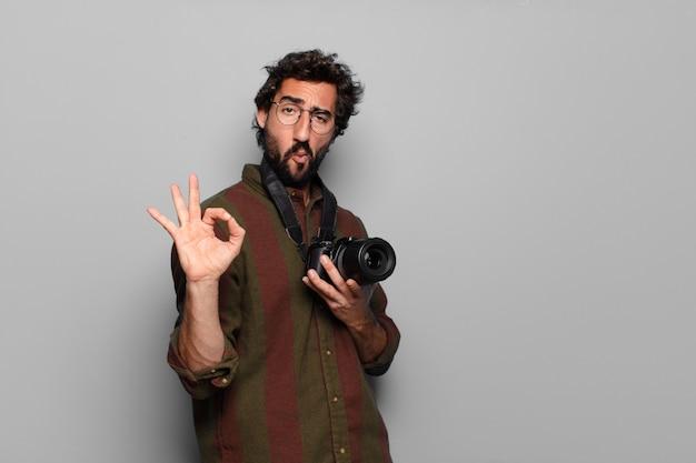 Jeune photographe barbu avec appareil photo donnant un geste ok