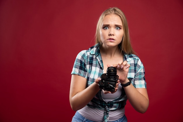 Jeune photographe blonde tenant un appareil photo professionnel et ne sait pas comment s'en servir.