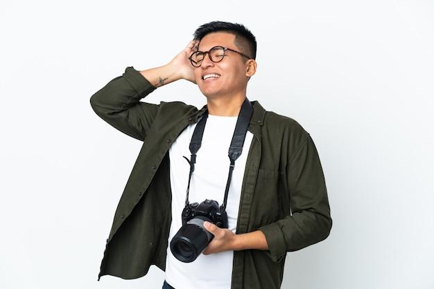 Jeune photographe équatorien isolé sur mur blanc souriant beaucoup