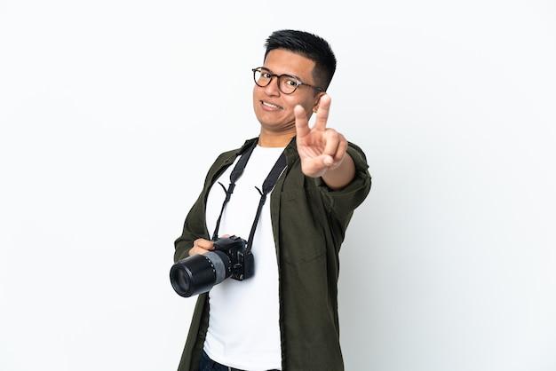 Jeune photographe équatorien isolé sur mur blanc souriant et montrant le signe de la victoire