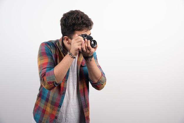 Jeune photographe expérimenté prenant des photos professionnelles de manière sérieuse.