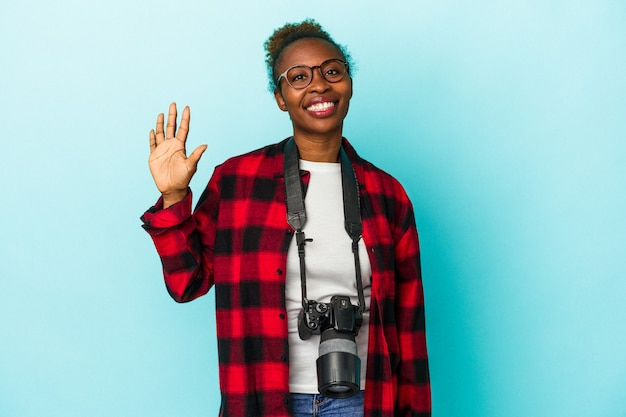Jeune photographe femme afro-américaine isolée sur fond bleu souriant joyeux montrant le numéro cinq avec les doigts.