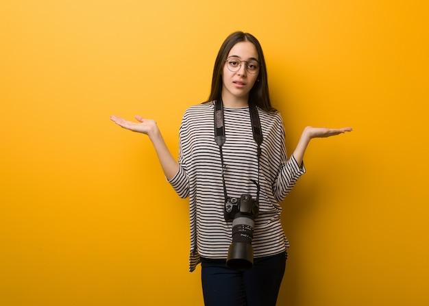 Jeune photographe femme doutant et haussant les épaules