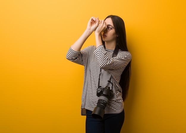 Jeune photographe femme faisant le geste d'une longue-vue