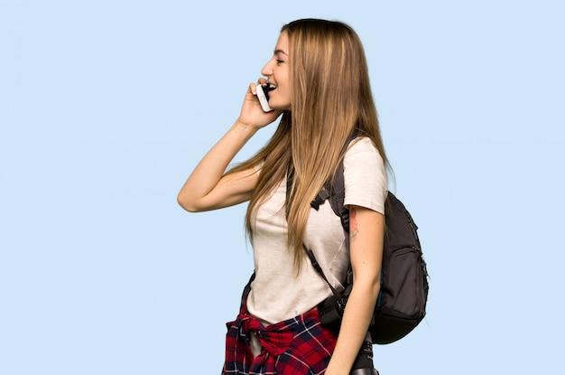 Jeune photographe femme gardant une conversation avec le téléphone portable sur le mur bleu isolé