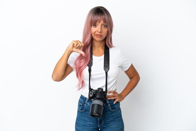 Jeune photographe femme métisse aux cheveux roses isolé sur fond blanc montrant le pouce vers le bas avec une expression négative
