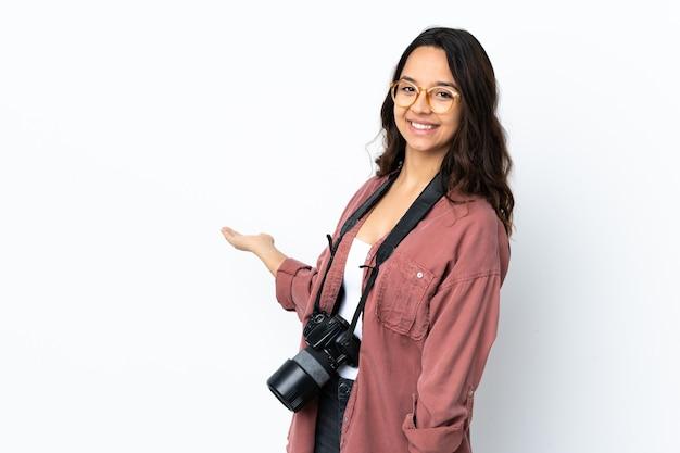 Jeune photographe femme sur mur blanc isolé étendant les mains sur le côté pour inviter à venir