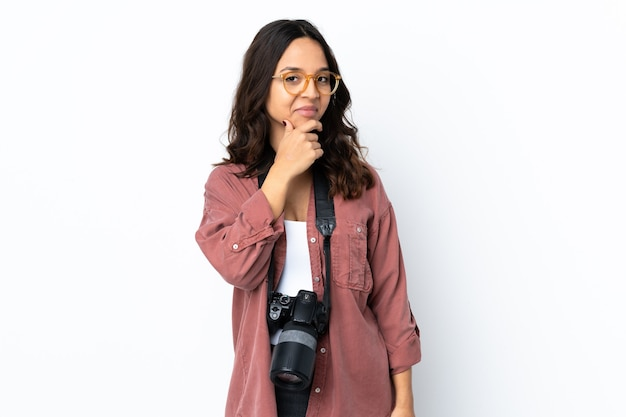 Jeune photographe femme sur mur blanc isolé pensant
