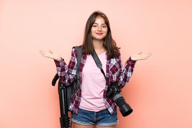 Jeune photographe fille isolée rose ayant des doutes avec une expression du visage confuse