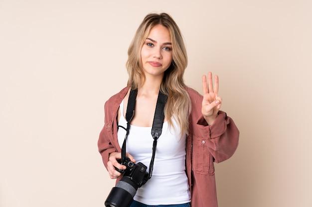 Jeune photographe fille sur mur heureux et en comptant trois avec les doigts