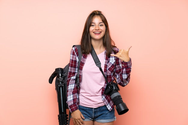 Jeune photographe fille sur mur rose isolé, geste de téléphone