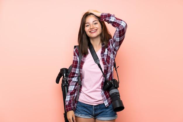 Jeune photographe fille sur mur rose isolé en riant