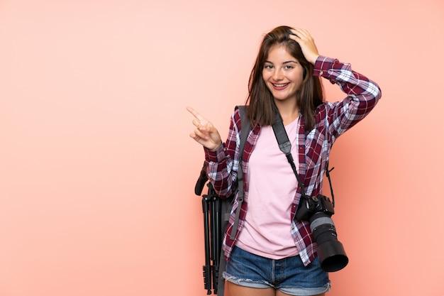 Jeune photographe fille sur mur rose isolé surpris et pointant le doigt sur le côté