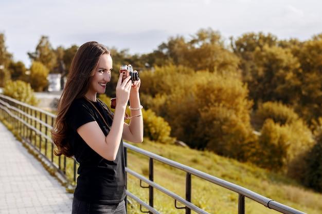 Jeune photographe heureuse se promène dans le parc avec appareil photo rétro