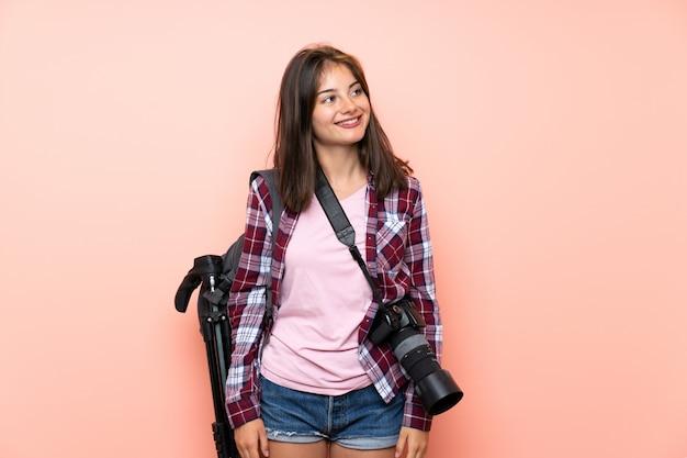 Jeune photographe photographe sur mur rose isolé en riant et levant