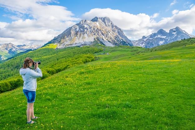 La jeune photographe photographie le sommet de la montagne komovi. monténégro.