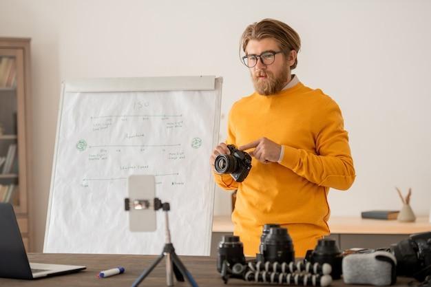 Jeune photographe professionnel contemporain tenant une photocaméra et expliquant son fonctionnement à son public en ligne lors de la leçon