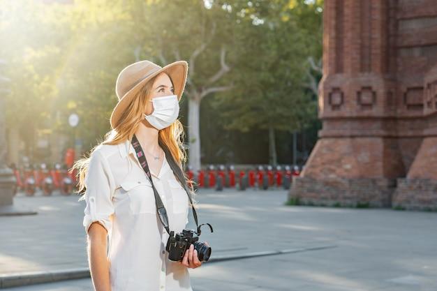 Jeune photographe professionnel féminin voyageant et prenant des photos portant un masque facial à l'extérieur.