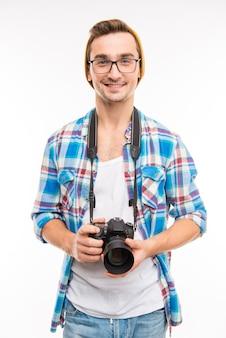 Jeune photographe souriant dans des verres avec appareil photo dans ses mains