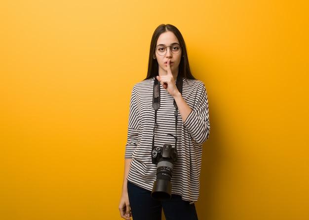 Jeune photographe tenant un secret ou demandant le silence