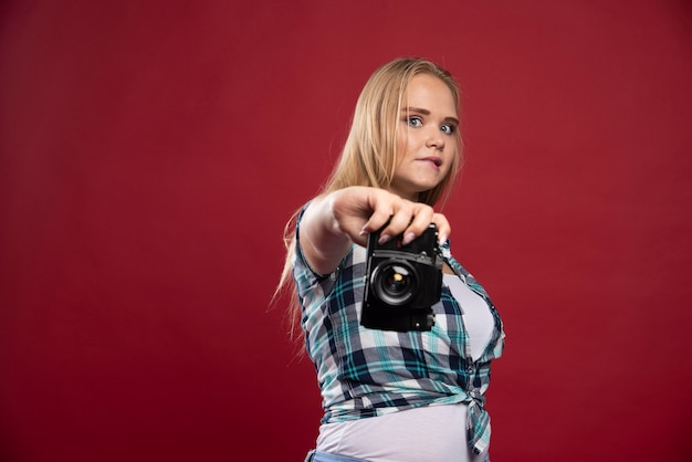 Jeune photographie blonde tenant un appareil photo professionnel et prend son selfie dans des positions étranges.