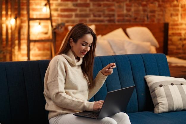 Jeune pigiste au bureau à domicile tenant une carte de crédit et utilisant un ordinateur portable