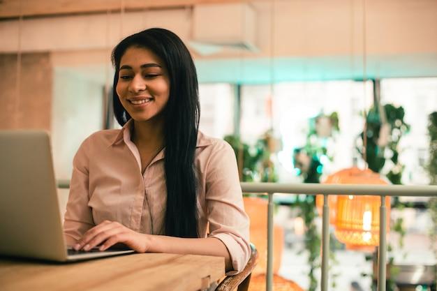 Jeune pigiste confiant assis à la table seul et souriant tout en regardant l'écran de l'ordinateur portable