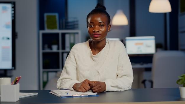 Jeune pigiste discutant en ligne avec un collègue assis devant la caméra dans un bureau de démarrage parlant lors d'une réunion virtuelle à minuit, faisant des heures supplémentaires