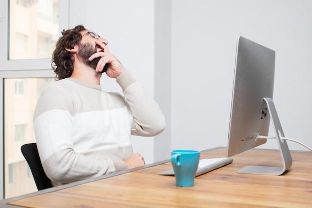 Jeune pigiste fou barbu travaillant avec son ordinateur