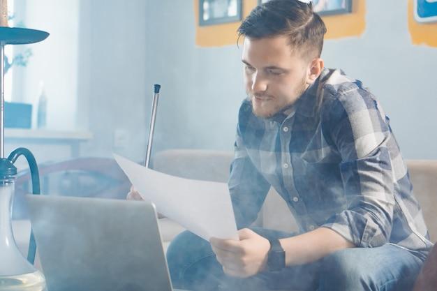 Jeune pigiste fumant une chicha et regardant un document tout en travaillant à domicile