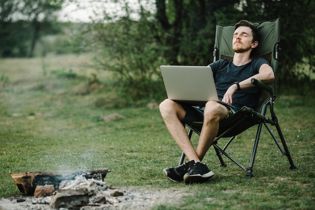 Jeune pigiste se détendre en forêt. homme travaillant sur ordinateur portable sur la nature. travail à distance, activité de plein air en été. voyage, randonnée, technologie, tourisme, concept de personnes - homme assis sur une chaise à l'extérieur.