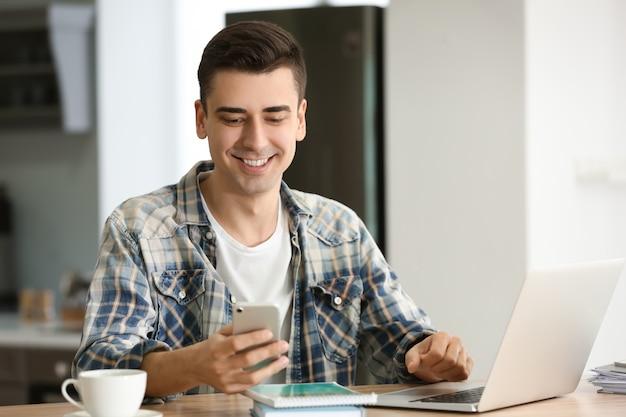 Jeune pigiste avec téléphone portable et ordinateur portable à la maison